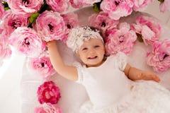 说谎在她的胃和微笑的女婴 免版税库存图片