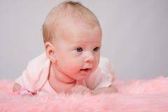 说谎在她的胃的两个月女孩她的头高 图库摄影