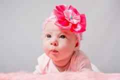 说谎在她的胃的两个月女孩她的头高 免版税图库摄影