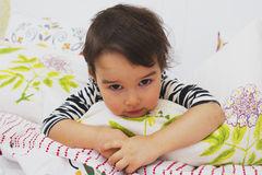 说谎在她的胃的小深色的女孩在床上 免版税库存图片