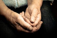 说谎在她的膝部的一个老妇人的手 定调子 库存图片