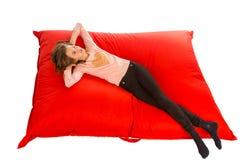 说谎在客厅或其他的红色装豆子小布袋沙发的梦中情人 库存图片