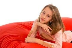 说谎在客厅或其他r的红色装豆子小布袋沙发的俏丽的女孩 免版税库存图片