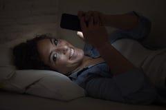 说谎在家庭长沙发的年轻美丽的妇女使用手机短信的微笑愉快 免版税库存图片