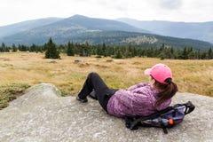 说谎在山,山Krkonose的岩石的妇女远足者 库存照片