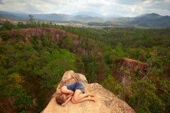 说谎在峡谷的岩石顶部的女孩 免版税库存图片