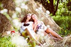 说谎在干草堆的两个女朋友 免版税图库摄影