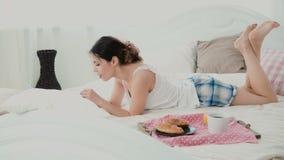 说谎在床上在早晨和聊天,使用那的膝上型计算机的美丽的女孩 吃新月形面包和键入的少妇 股票录像