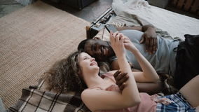 说谎在床上的不同种族的夫妇 笑,使用智能手机的男人和妇女 男性和女性一起花费时间 免版税库存照片