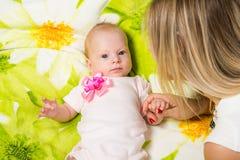 说谎在床上的两个月婴孩,坐在妈妈旁边 免版税库存图片