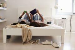 说谎在床上的十几岁的女孩使用电话和片剂计算机 免版税库存照片