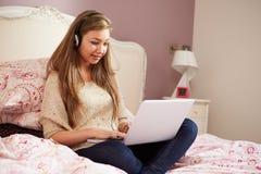 说谎在床上的十几岁的女孩使用膝上型计算机佩带的耳机 免版税库存照片
