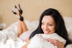 说谎在床上的女用贴身内衣裤的妇女在她的卧室 免版税库存照片
