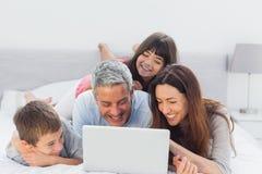 说谎在床上的家庭使用他们的膝上型计算机 库存照片