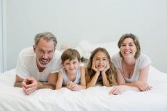 说谎在床上的微笑的家庭画象在卧室 库存图片