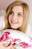 说谎在床上的蓝眼睛美丽的愉快的微笑的迷人的年轻白肤金发的妇女特写镜头画象拿着枕头和查寻 图库摄影