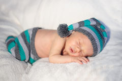 说谎在床上的被编织的帽子的小男婴 免版税库存图片