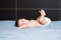 说谎在床上的逗人喜爱的亚裔婴孩 免版税图库摄影