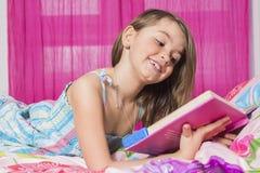 说谎在床上的逗人喜爱的女孩微笑对照相机 图库摄影