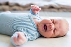 说谎在床上的逗人喜爱的新出生的男婴,哭泣 关闭 库存照片