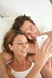 说谎在床上的年轻夫妇使用智能手机 免版税库存照片