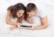 说谎在床上的年轻夫妇使用片剂个人计算机 免版税库存照片