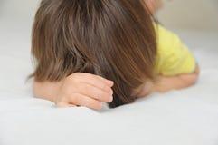 说谎在床,哭泣的被触犯的小女孩上的儿童掩藏的面孔 图库摄影