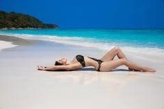 说谎在异乎寻常热带的黑比基尼泳装的美丽的性感的妇女是 免版税库存图片