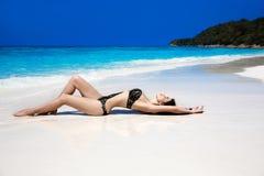 说谎在异乎寻常的热带海滩的美丽的性感的比基尼泳装模型妇女 免版税库存图片