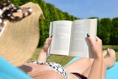 说谎在懒人在庭院里和读书的妇女 库存照片