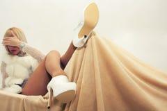 说谎在扶手椅子的性感的白肤金发的妇女 免版税库存照片