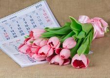 说谎在日历的桃红色郁金香花束  免版税库存照片