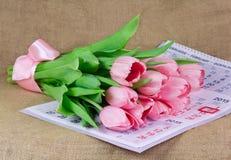 说谎在日历的桃红色郁金香花束  库存图片