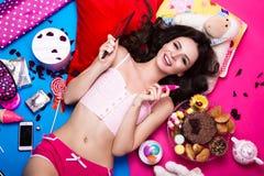 说谎在明亮的背景的美丽的新鲜的女孩玩偶围拢由甜点、化妆用品和礼物 时尚秀丽样式 库存图片