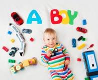说谎在有上面信件的毯子的男婴 免版税库存照片