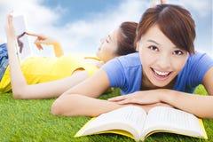 说谎在有书的草原的微笑的俏丽的学生 免版税库存图片