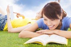 说谎在有书的草原的微笑的俏丽的学生 库存照片