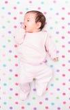 说谎在有五颜六色的圆点的毯子的小婴孩 免版税库存照片