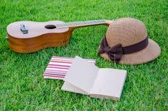 说谎在有可爱的帽子和笔记本的草甸的尤克里里琴。 库存照片