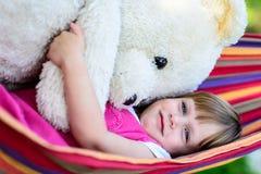 说谎在有大玩具熊的吊床的小逗人喜爱的女孩 免版税库存照片