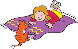 说谎在有她的猫的一张席子的女孩 库存照片