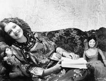 说谎在有她的玩偶的沙发的中国印刷品礼服的妇女和书(所有人被描述不是更长生存和没有ES 库存图片