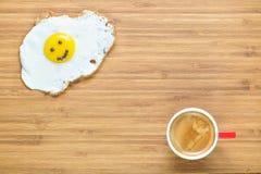 说谎在有小红色咖啡的一个木切板的微笑的煎蛋在它附近 经典早餐概念 免版税库存照片