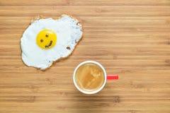 说谎在有小红色咖啡的一个木切板的微笑的煎蛋在它附近 经典早餐概念 库存图片