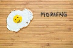 说谎在有早晨题字的一个木切板的微笑的煎蛋在它附近 经典早餐概念 库存图片