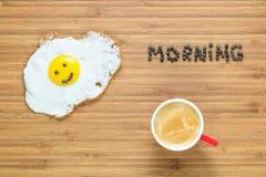 说谎在有早晨题字的一个木切板的微笑的煎蛋在它附近 经典早餐概念 免版税库存图片