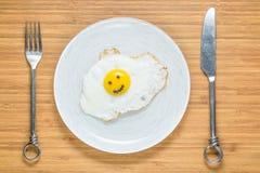 说谎在有早晨题字的一个木切板的微笑的煎蛋在它附近 经典早餐概念 免版税库存照片