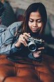 说谎在有照片照相机的皮革沙发的华美的女孩在她的手上 免版税库存照片