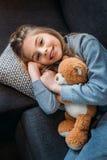 说谎在有玩具熊的长沙发和微笑对照相机的小女孩 免版税库存图片