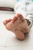 说谎在有肮脏的脚的沙发 图库摄影